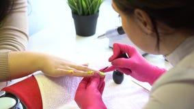 El primer tiró de un cosmetólogo que aplicaba esmalte de uñas al clavo femenino en un salón del clavo Ciérrese para arriba de una almacen de video