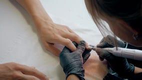 El primer tiró de un cosmetólogo que aplicaba esmalte de uñas al clavo femenino en un salón del clavo Mujer que consigue la manic almacen de metraje de vídeo