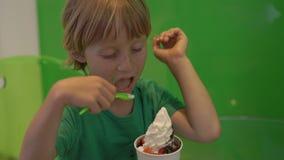 El primer tiró de un niño pequeño que comía el helado delicioso del yogurt congelado almacen de video