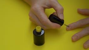 El primer tiró de una muchacha que pinta sus clavos en amarillo en un fondo amarillo concepto amarillo metrajes