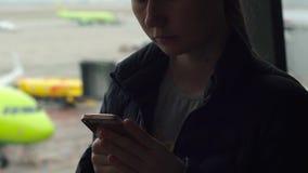 El primer tiró de una mujer joven que usaba un smartphone delante de una ventana grande en un aeropuerto almacen de metraje de vídeo