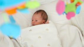 El primer tiró del bebé lindo de 1 mes que mentía debajo de la manta en pesebre con el móvil de giro almacen de metraje de vídeo