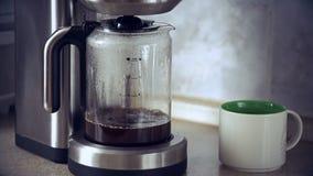 El primer tiró del café que preparaba en fabricante de café y que fluía adentro a la garrafa almacen de video