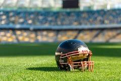 el primer tiró del casco de fútbol americano americano que mentía en hierba verde imagenes de archivo