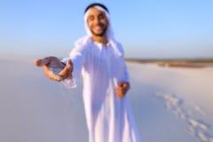 El primer tiró del retrato y de manos del individuo árabe joven en d arenosa Fotos de archivo libres de regalías