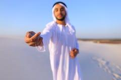 El primer tiró del retrato y de manos del individuo árabe joven en d arenosa Imagen de archivo libre de regalías