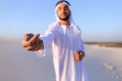 El primer tiró del retrato y de manos del individuo árabe joven en d arenosa Foto de archivo libre de regalías