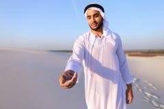 El primer tiró del retrato y de manos del individuo árabe joven en d arenosa Imagen de archivo