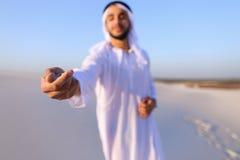 El primer tiró del retrato y de manos del individuo árabe joven en d arenosa Fotografía de archivo