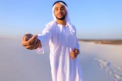 El primer tiró del retrato y de manos del individuo árabe joven en d arenosa Foto de archivo