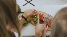 El primer tiró las manos de las muchachas de las adolescencias que usaban el cuchillo de cocina que aprendía cortar la verdura de almacen de metraje de vídeo