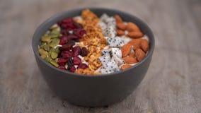 El primer tir? de un cuenco del smoothie con la papaya, la fruta del drag?n, el granola, la cereza secada, y las semillas de cala almacen de video