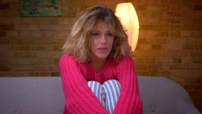 El primer tirado de ama de casa relajada en suéter rosado mira atento la película en el hogar acogedor metrajes