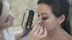 El primer tirado de artista de maquillaje de arriba a abajo termina maquillaje, sostiene una paleta de sombras secas desnudas en  almacen de video