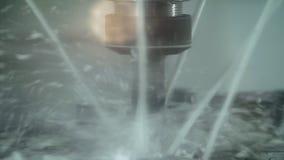 El primer tirado de la chapa cortada con agua salpica en fondo borroso de la fábrica metrajes