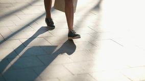 El primer tirado de la mujer en zapatos azules y blancos está caminando a lo largo de la calle soleada Ninguna cara almacen de video