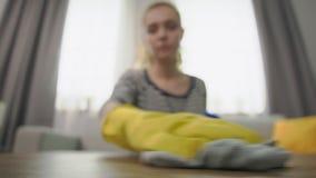 El primer tirado de mujer atractiva limpia una mesa de centro con un trapo almacen de metraje de vídeo