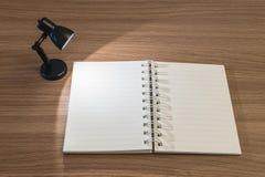 El primer un cuaderno con la luz de la pequeña lámpara en el cuarto oscuro en el escritorio de madera texturizó el fondo Fotos de archivo