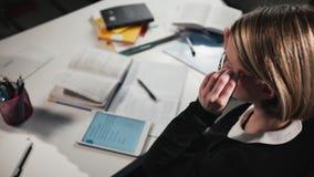 El primer una colegiala o un estudiante que limpia los vidrios utiliza una tableta y escribe en un libro de trabajo Ella ` s que  metrajes