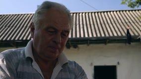 El primer, viejo hombre concentrado limpia el espárrago del faisán almacen de metraje de vídeo