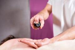 El primer vierte el aceite en la palma Osteópata que hace masaje manipulador en el abdomen femenino Manos del hombre que dan masa Imagenes de archivo
