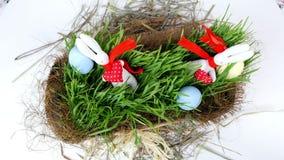 El primer, visión desde arriba, rotación, la composición festiva de pascua consiste en los huevos coloreados, hierba del verde y  almacen de metraje de vídeo