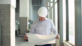El principal arquitecto considera el modelo del edificio comercial que se coloca dentro el constructor mira los planes para el fu almacen de video