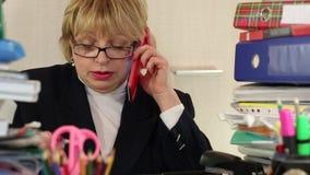 El principal contable de la mujer mayor en vidrios y con smartphone rojo se sienta en la tabla almacen de metraje de vídeo