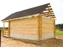 El principio de la construcción de una casa de madera La barra se perfila y cae en el surco Colocación en la esquina medio imagen de archivo libre de regalías
