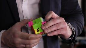 El problema y soluciona El hombre de negocios da solucionar rompecabezas del cubo del ` s de Rubik en la oficina almacen de video