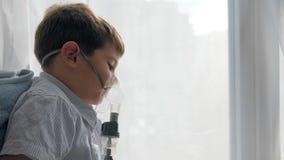 El procedimiento de los nebulizadores, niño enfermo respira a través del compresor de los inhaladores para las enfermedades respi almacen de metraje de vídeo