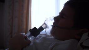El procedimiento del nebulizador, muchacho de dolor del niño en máscara respira a través del inhalador con la medicación para pre almacen de metraje de vídeo