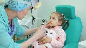 El procedimiento médico, otorrinolaringólogo trata al niño, niño del examen médico, otorrinolaringólogo del consejo en la clínica almacen de metraje de vídeo