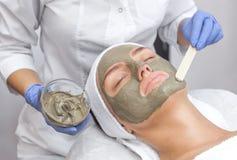 El procedimiento para aplicar una máscara de la arcilla a la cara de una mujer hermosa fotos de archivo libres de regalías