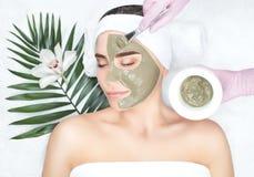 El procedimiento para aplicar una máscara de la arcilla a la cara de una mujer hermosa imagen de archivo