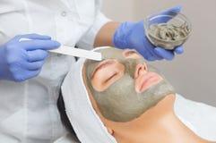 El procedimiento para aplicar una máscara de la arcilla a la cara de una mujer hermosa imagen de archivo libre de regalías