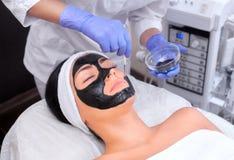 El procedimiento para aplicar una máscara negra a la cara de una mujer hermosa foto de archivo libre de regalías