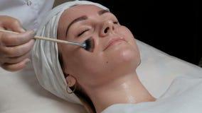 El procedimiento para limpiar la piel de la cara en un salón de belleza o un centro de la cosmetología Primer de un cr de extensi metrajes