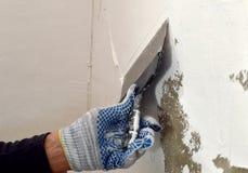 El proceso de aplicar una masilla blanca en la pared gris concreta Foto de archivo