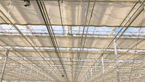 El proceso de cerrar el tejado en un invernadero moderno grande Cierre del tejado en un invernadero moderno grande almacen de metraje de vídeo