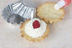 El proceso de cocinar las tortas poner crema Foto de archivo libre de regalías