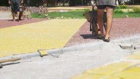 El proceso de construcción, reparando la acera Trabajador que pone la piedra que pavimenta en un parque de la ciudad metrajes