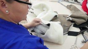 El proceso de crear un abrigo de pieles: costura y el cortar almacen de metraje de vídeo