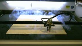 El proceso de crear una parte de madera en una máquina herramienta CNC del laser, cortando una parte de un árbol por una máquina  almacen de metraje de vídeo