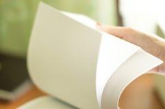 El proceso de dar vuelta el papel blanco de la oficina Fotografía de archivo libre de regalías