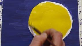 El proceso de dibujar un sol o una luna amarillo en un fondo azul con las pinturas, aguazo
