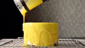 El proceso de echar el esmalte del espejo en una sesión redonda de la torta mousse amarillo almacen de metraje de vídeo