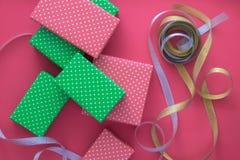 El proceso de envolver y de empaquetar los regalos de la Navidad y del Año Nuevo Cajas y cintas en un fondo blanco o rosado Endec Fotografía de archivo libre de regalías
