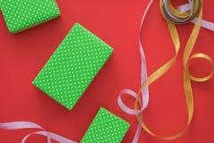 El proceso de envolver y de empaquetar los regalos de la Navidad y del Año Nuevo Cajas y cintas en un fondo rojo Endecha plana, v Foto de archivo libre de regalías
