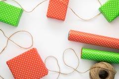 El proceso de envolver y de empaquetar los regalos de la Navidad y del Año Nuevo Cajas, papel del diseñador, guita en un fondo bl Imagen de archivo libre de regalías